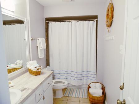 Click to enlarge image Bathroom with new tub and tiled surround - Wahoo Quarters - One bedroom, one bath, LARGE condo with laundry, tile floors, Dog Friendly. Walk to beach